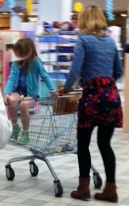 """Una bambina di 7-8 anni impesta il cesto del carrello con le suole delle scarpe e corre il rischio di farlo ribaltare procurandosi lesioni anche gravi; ma questa mamma così alla moda evidentemente non ne è consapevole... E lasciamo poi perdere il messaggio che la mamma trasmette alla ragazzina: """"Tu sei ancora una bambina di un anno e mezzo!"""""""