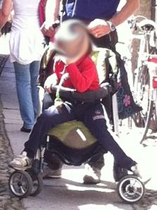 Un bambino italiano di 3-4 anni nel passeggino: la situazione è oltretutto ridicola perché non ci sta proprio!